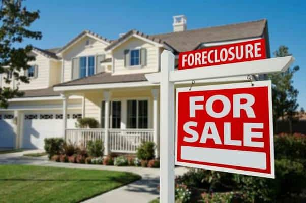 cream foreclosed home sold sign at front