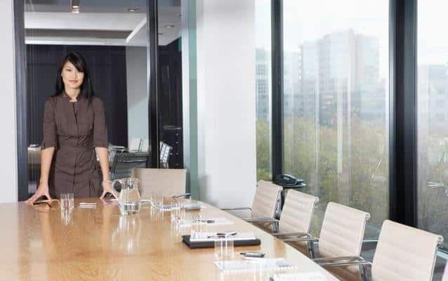 business coach lady staning by table in boardroom